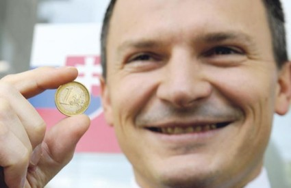Jan Pociatek, slovački ministar financija, pozira s eurom