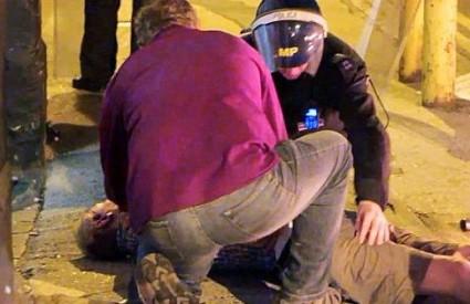 Prolaznik i policajac pokušavaju pomoći teško ozlijeđenom muškarcu